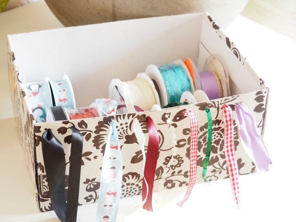 sortierte und entwirrte Dekobänder in einer Box mit Löchern am Rand, durch die die Borten gefädelt werden